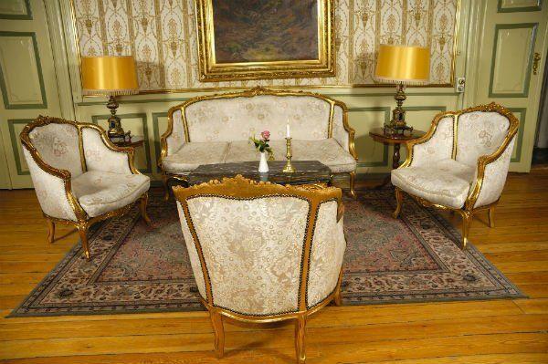 un divano e tre poltrone in legno e dorato