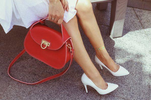 Giovane donna con una borsa rossa e le scarpe con i tacchi alti a Monterotondo