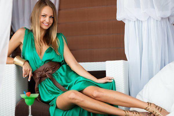 Giovane donna in abito verde seduta sul divano a Monterotondo
