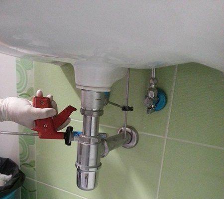 una mano con una pistola rossa da disinfezione sotto un lavabo