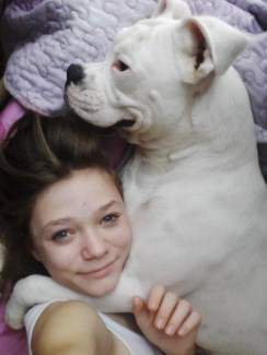 White Boxer dog hugging young girl
