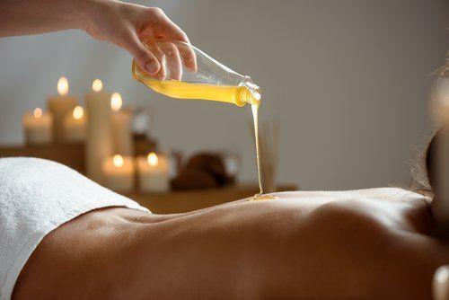 Una massaggiatrice versa dell'olio sulla schiena di una donna sdraiata