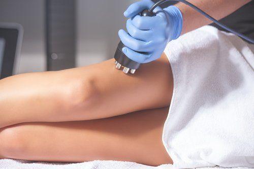 Massaggiatrice effettua una radiofrequenza su una gamba