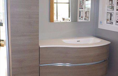 un mobile in legno e un alloggio lavabo in un bagno