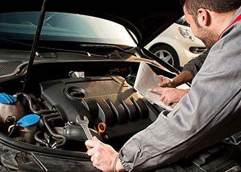 due meccanici consultano un foglio durante una manutenzione a un auto