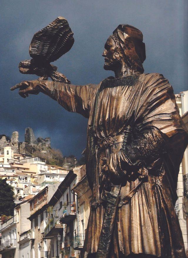 una scultura di un uomo con la barba con il braccio in avanti e sopra un'aquila