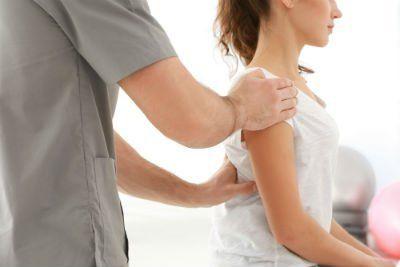 medico esegue manovra di rieducazione posturale su giovane paziente