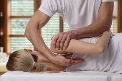 fisioterapista esegue manovra alla schiena di una paziente