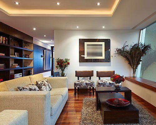 una sala con un divano, due poltrone e una libreria