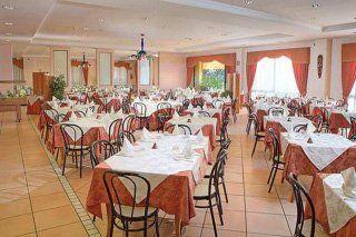 dei tavoli apparecchiati con delle tovaglie di color bianco e rosa