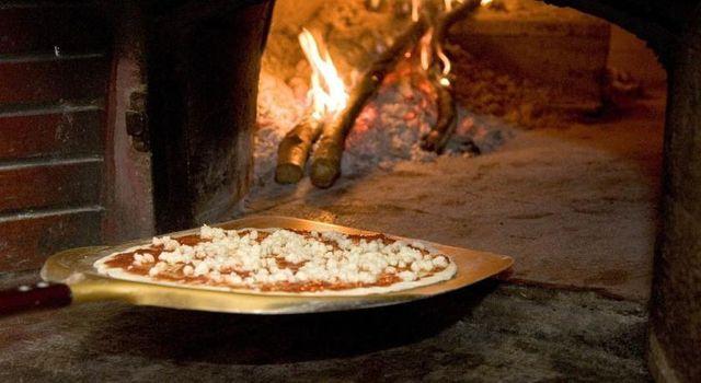 una pizza viene messa dentro un forno a legna