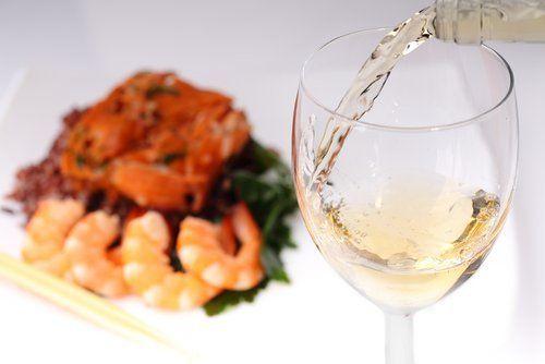 primo piano del vino che viene versato in un bicchiere e come sfondo piatto di pesce misto