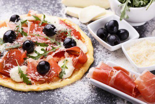 preparazione di pizza con olive, verdure e prosciutto crudo