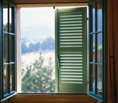 una finestra aperta con vista di un'anta di una persiana verde