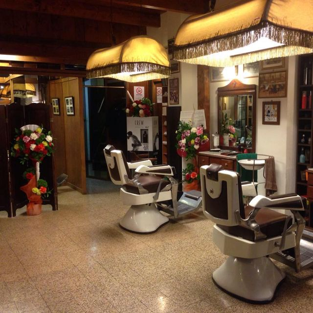 prima barbiera in Italia che taglia barba a un cliente