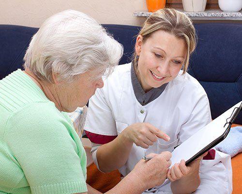 una signora anziana che compila un modulo e accanto un infermiera