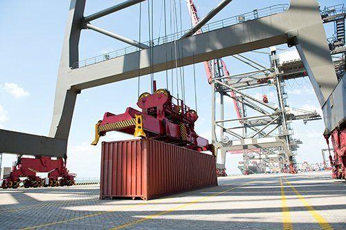 una gru che sta per sollevare un container rosso