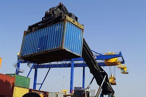 una gru solleva un container blu