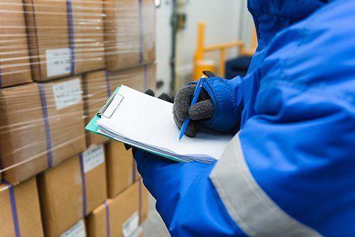 addetto durante un controllo in magazzino compila un documento