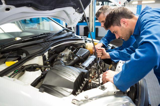 Due meccanici lavorano sul motore di un'auto