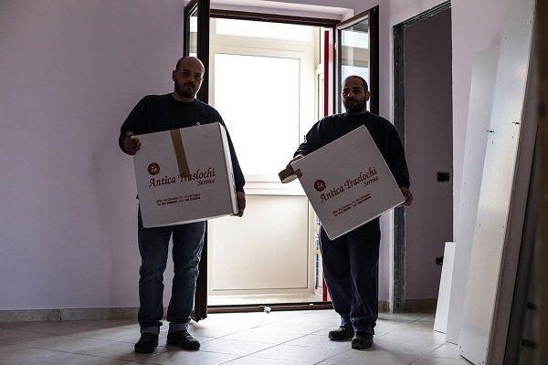 Due uomini con degli scatoloni in mano con scritto Antica traslochi