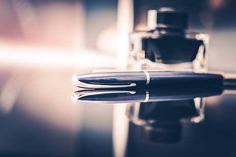 Una penna a sfera con calamaio sullo sfondo