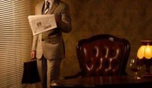 Un professionista nel suo studio che regge una valigetta mentre legge il giornale