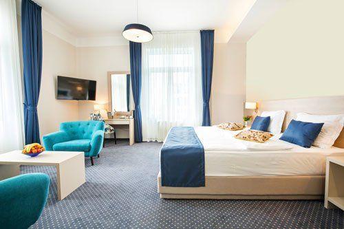 Ampia camera da letto in tono chiaro con dettagli blu come i cuscini,le tende e le poltrone