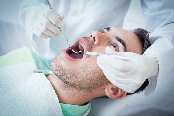 Un ragazzo con la bocca aperta mentre un dentista lo visita