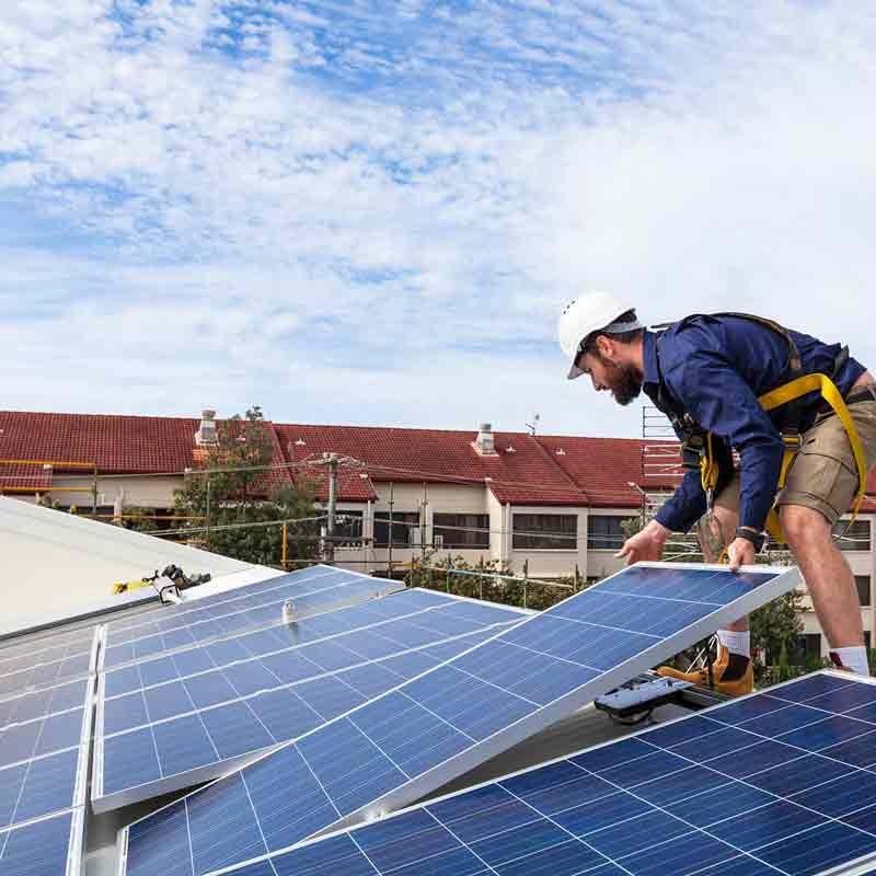 Worker installing solar panels in Brisbane South