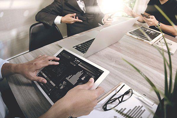 delle persone alla scrivania con dei tablet e dei pc