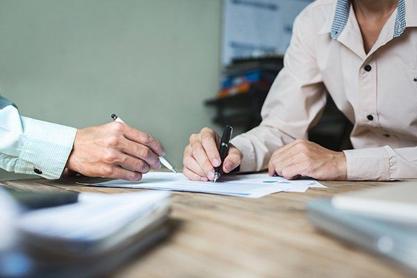 una mano che con una penna indica un foglio e un'altra che scrive