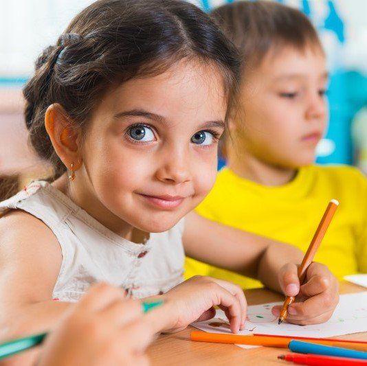 Bambina alla scuola materna disegna