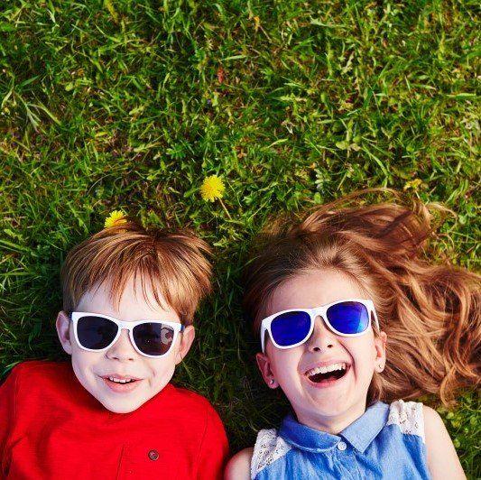 Due bambini ridono stesi su un prato verde