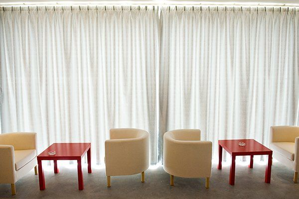 Ufficio bar-caffetteria con comode sedie e tavolo rossa accanto a tenda