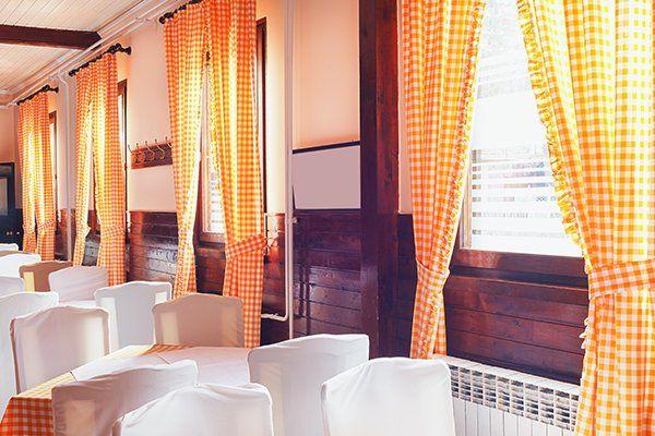 ristorante interno con tende in stile antico e mobili in bianco
