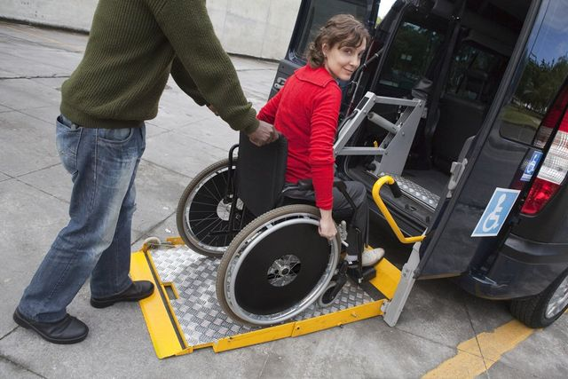 Woman in a wheelchair getting up a ramp of a van
