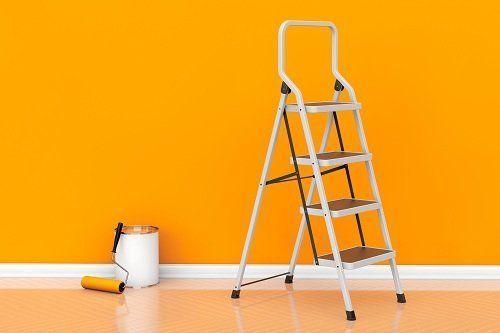 un secchio con un rullo, una scaletta e una parete arancione