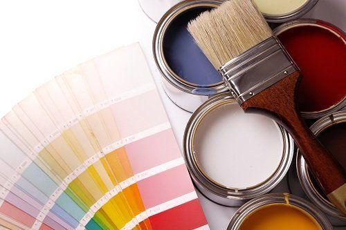 un pennello,dei barattoli di vernice e degli esempi di colore