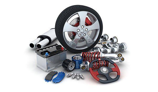 un pneumatico con cerchione,delle sospensioni, un terminale di scarico, un volante bordeaux e nero e  una batteria da macchina-Iper gomme-Morbegno