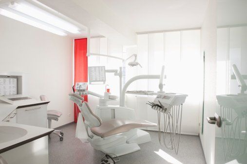 interno dello studio dentistico con un lettino arancione, apparecchiature, sulla destra una scrivania angolare con monitor, una cassettiera e un pavimento in parquet