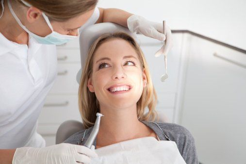 un dentista mentre visita una donna sdraiata