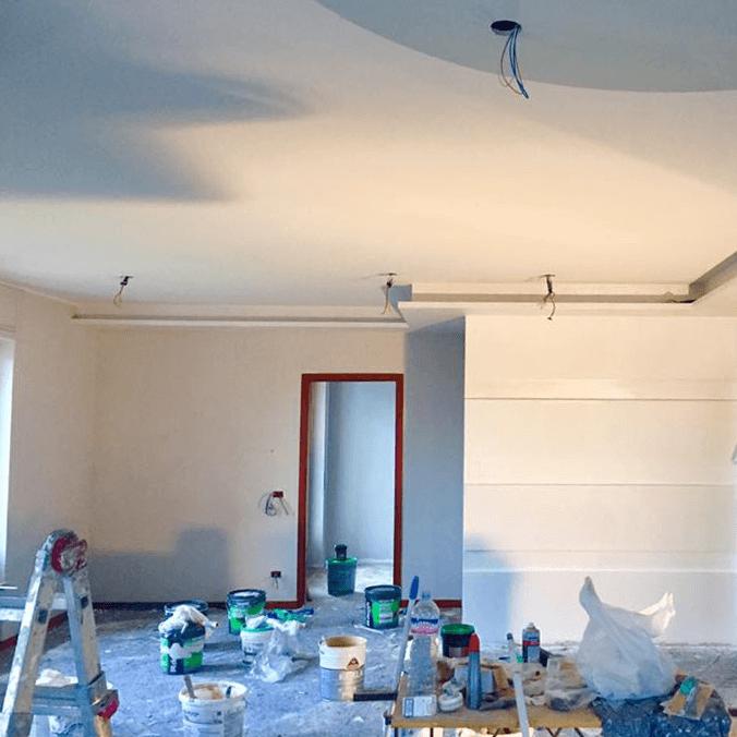 stanza in fase di ristrutturazione con secchi di pittura sul pavimento