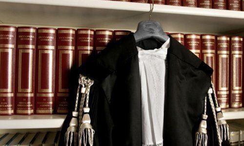 Toga di giudice davanti a una biblioteca di giurisprudenza