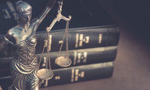 Bilancia della giustizia accanto a libri di giurisprudenza