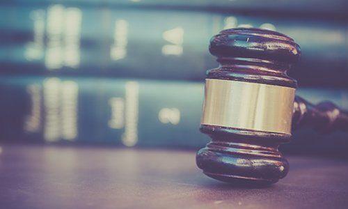 Maza de la giustizia accanto a libri di giurisprudenza