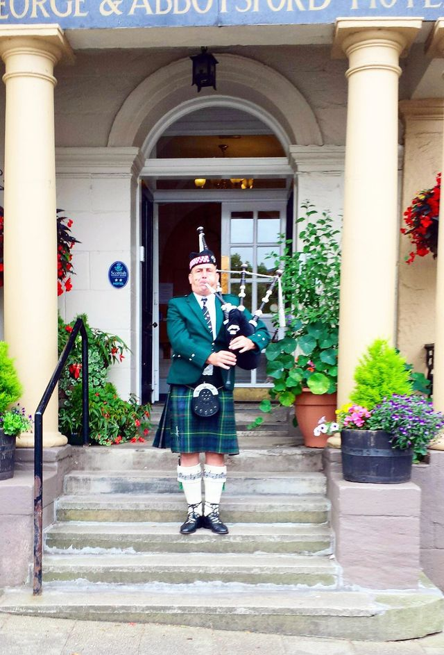 A traditional bagpipe player outside the George & Abbotsford Hotel