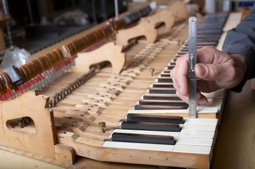 Piano technician at work checking key, DOF focus on hand