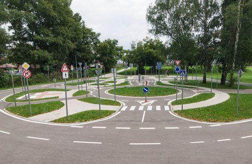 una rotonda con delle aiuole, dei segnali stradali e vista degli alberi