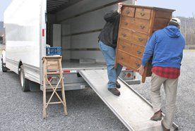 Two men loading a chest of drawers onto a removal van